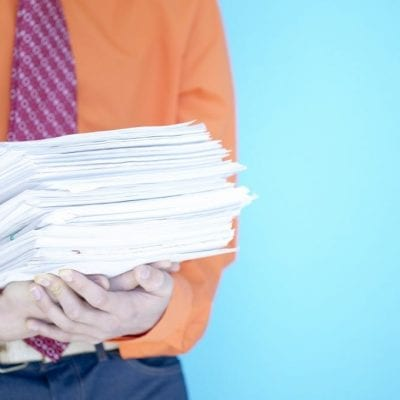 Man holding pile of paper